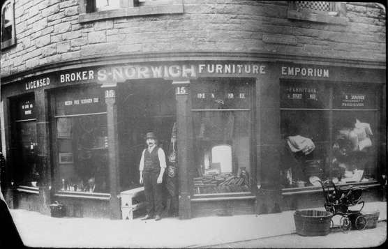 """Lithuanian Shopkeeper, Church Street, Leith, c.1900 """"There are about 200 families of Russian and Polish Jews in Edinburgh and Leith, and they are all employed. [Only] 10 or 12 men and women passed through the city from Hamburg to the Clyde to set sail for America."""" (1894) Shipping records show that the majority of Jews landing at Leith Docks passed through Edinburgh on their way to Glasgow in order to continue their journey to the USA. Others remained, either because they could afford to go no further or because Edinburgh was their destination. credit: Courtesy of National Museums Scotland"""